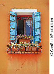 Window on a orange wall, decorated with flowers