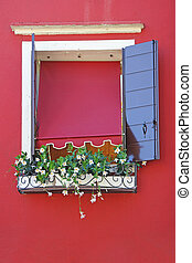 Window on a red wall, decorated with flowers