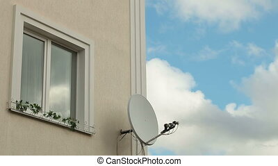 Window on wall of a house with satellite dish against sky with clouds