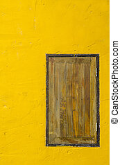 Window on yellow cement wall