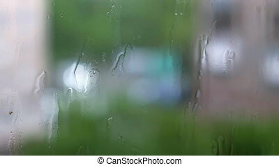 Window Rain Background Defocused. Cars passing by and shining headlights