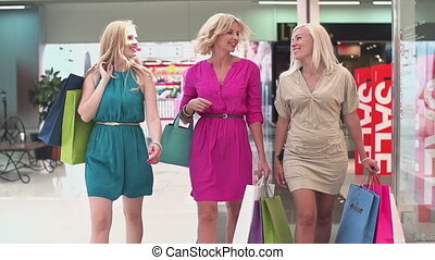 Three ladies approaching camera with shopping bags in slow motion