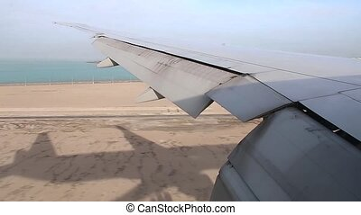airplane wing on window view during plane landing on Hamad International Airport runway, Aerial shot at a low height of the sea and desert.
