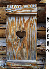Window shutter with heart of a wooden log cabin in the European Alps