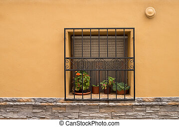 Window with flower pots on a Mediterranean facade