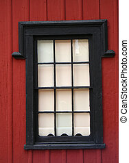 window trimmed in black against red siding, six over six