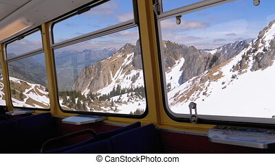 Window view of a Moving Mountain Train on the Snowy Switzerland Alps. Montreux City.
