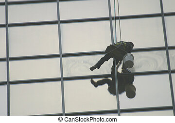 window washer - A window washer works high above the city...