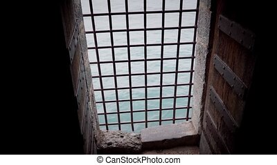 window with bars in a prison cell of fortress Chillon castle, Switzerland, on the shores of Lake Geneva