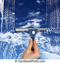 Window with blue sky and white clouds - Hand cleaning window...