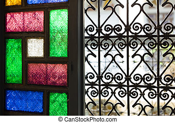 Window with colored glass and arabic grill in Marrakesh,...