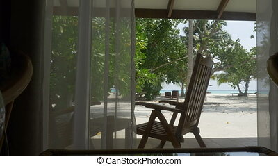 Window with curtain overlooking a beautiful beach with palm trees and ocean.