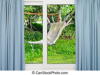 window with curtains overlooking the garden with a hammock -...