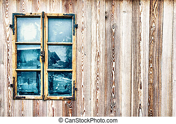 Window with decorated frame on wooden wall