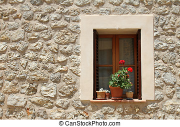 Window with flower pots on the stone building wall