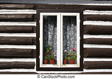 window with flowers in wall of old wooden house