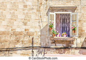 Window with flowers on the background of a white stone wall typical of architecture in Croatia