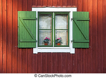 Window with green shutters on red wooden wall
