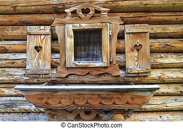 Window with heart shutters of a wooden log cabin in the European Alps