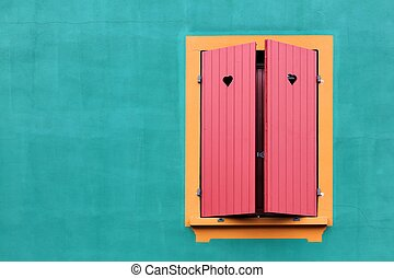 Window with red shutters and small hearts on a green wall
