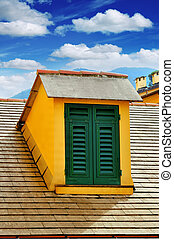 window with shutters on the roof on blue sky background