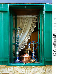 Window with wooden shutters and hookahs on inside sill