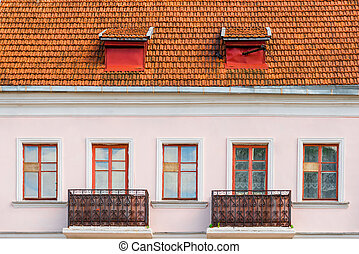 windows and balconies on the wall of an old house on the top floor