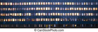 Windows glowing in the night on an office building