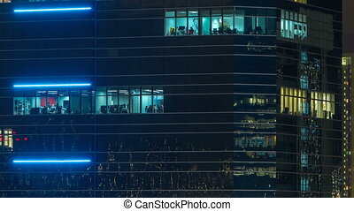 Windows in modern city office building at night timelapse.