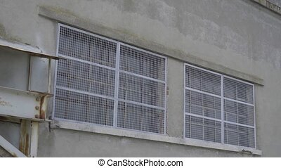 Windows of a factory closes by wire mesh - Windows of an ...