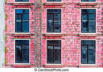 Windows of a house under construction from cinder blocks painted red.
