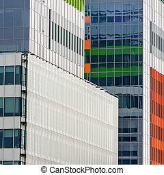 Windows of a modern business building exterior. Vertical image of abstract modern building background for design with colorful windows.