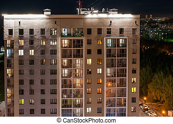 Windows of a multi-storey building with balconies in the evening