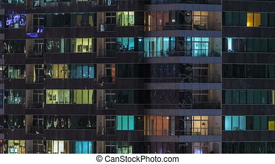 Windows of the multi-storey building of glass and steel lighting inside and moving people within timelapse
