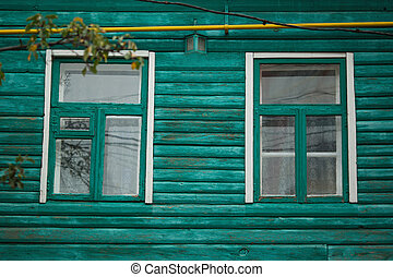 Windows on the facade of an old wooden house.