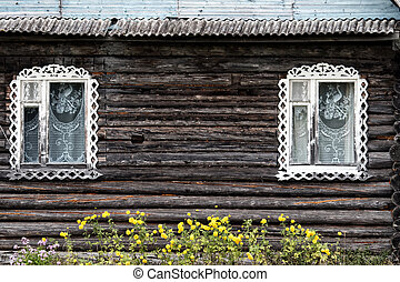 North-West Russia wooden architecture. Old log cabin and carved window frames. Photo in vintage style