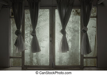 Windows with the curtain in an abandoned house