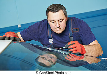 Automobile glazier repair windscreen or windshield of a car in auto service station garage