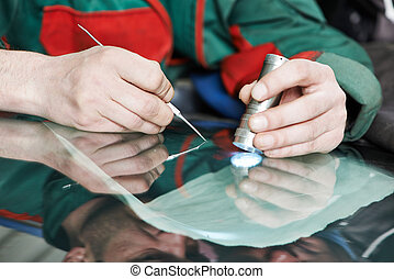 Automobile glazier worker fixing and repair windscreen or windshield of a car in auto service station garage