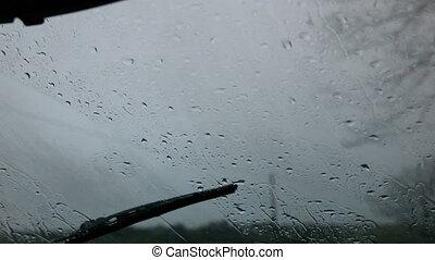 Windscreen wiper wiping rain away from car window in slow ...