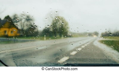 Windscreen wipers cleaning windshield glass on rainy day. -...