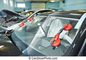 Automobile car windshield or windscreen service concept in auto service station garage