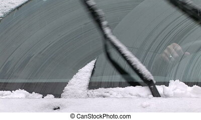 Windshield wipers clearing off the snow