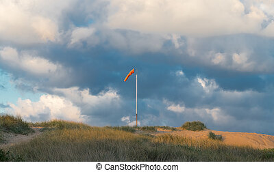 Windsock blowing on a sand dune with clouds in the background.