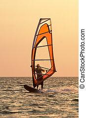 Windsurfer on waves of a gulf on a sunset
