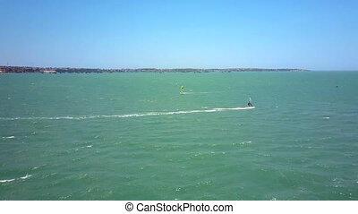 windsurfer rides azure ocean waves under blue sky -...