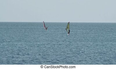 Windsurfer sail the wind to horizont at day