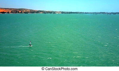 windsurfer sails in open ocean against distant coast - high...