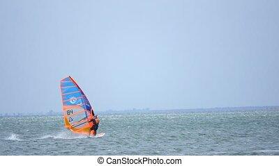 Windsurfer silhouette over sea