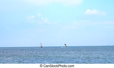 Windsurfer silhouette over sea